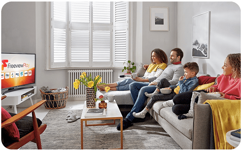Family sitting on a sofa watching TV