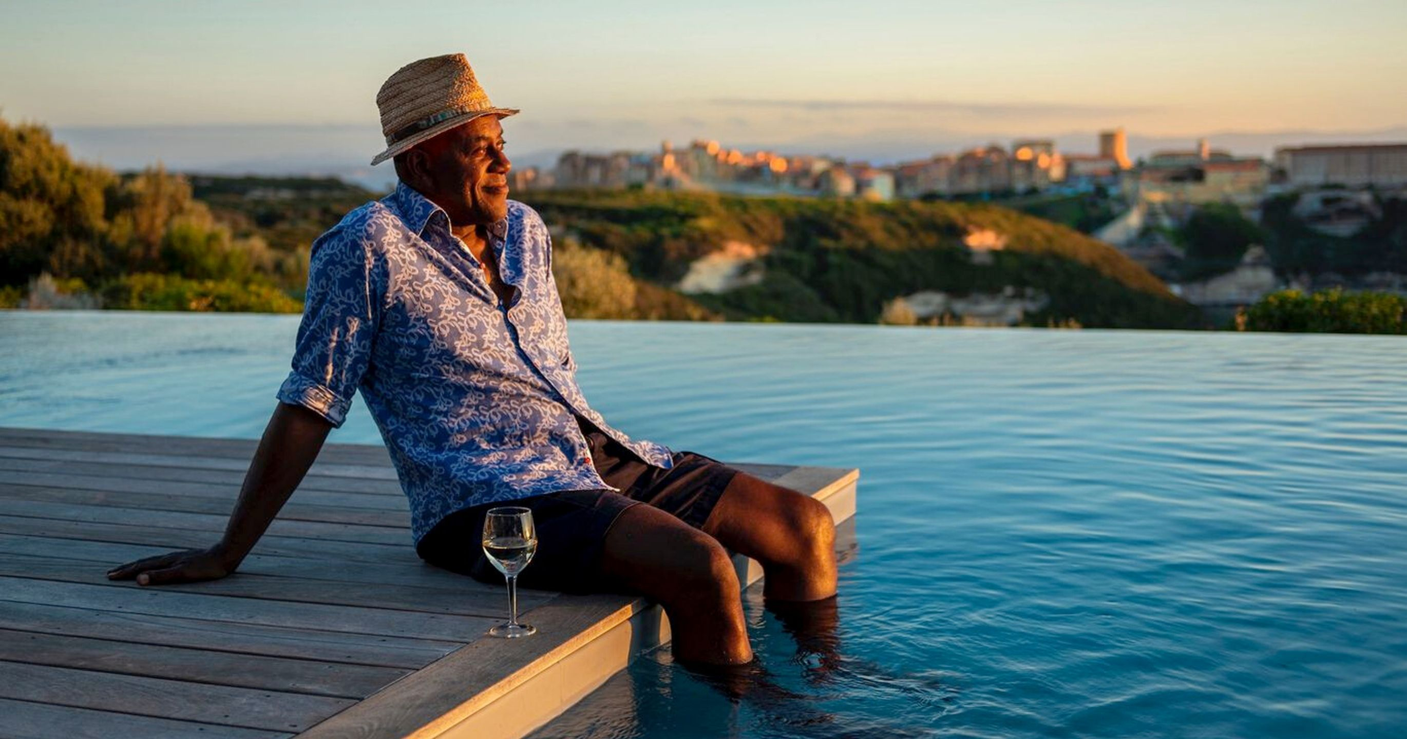 Ainsley Harriot sits with his legs in a swimming pool enjoying a glass of wine