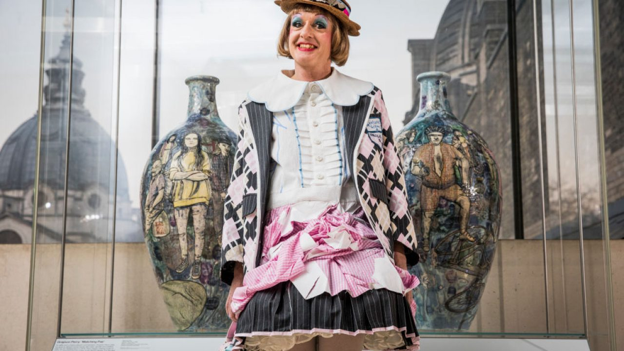 Grayson Perry wearing a colourful dress, in front of a mirrored building