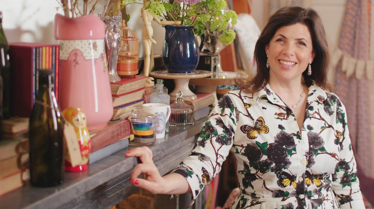 Kirstie Allsopp in front of a mantelpiece full of ornament