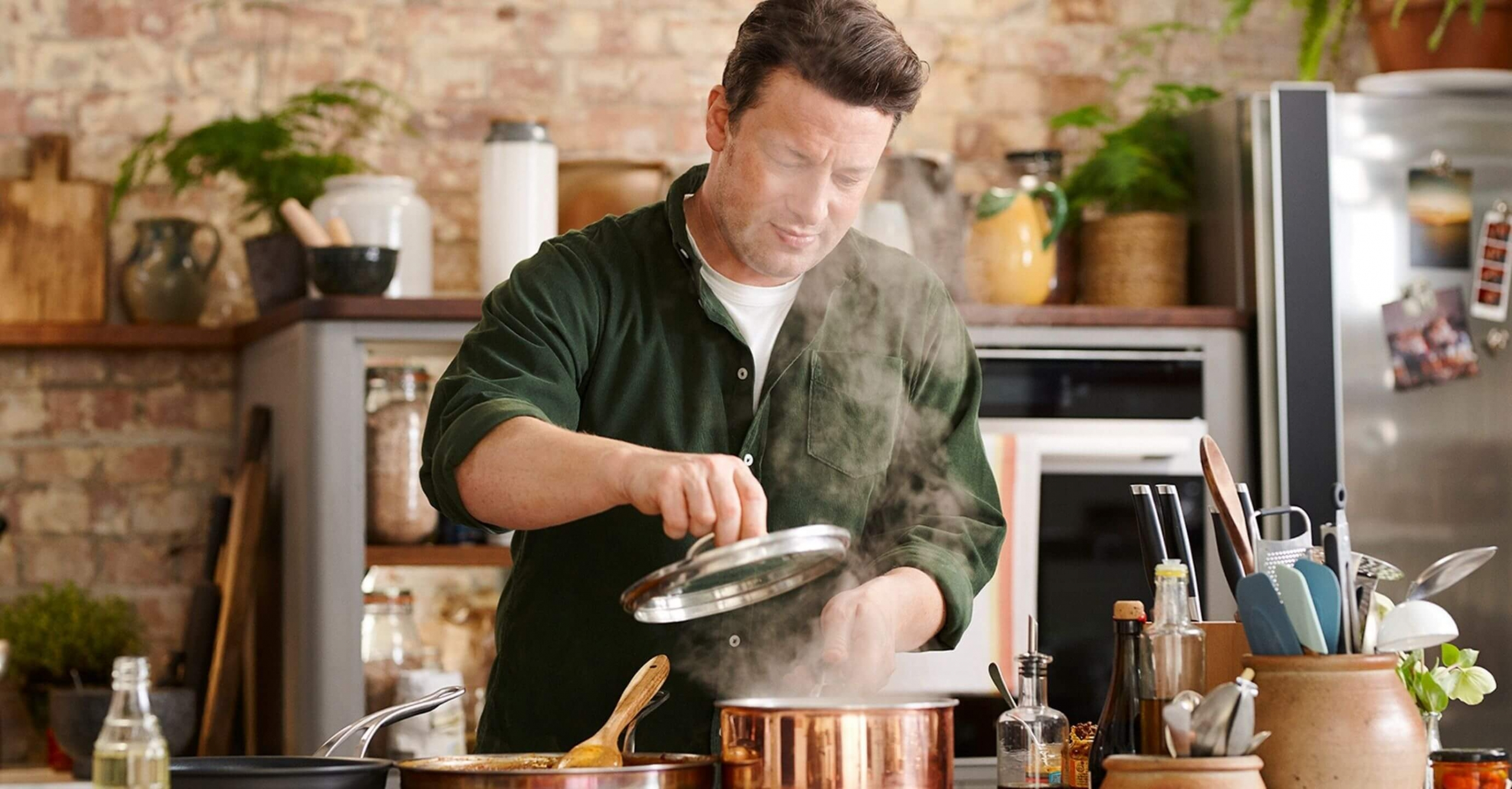 "Jamie Oliver, presenter of ""Keep cooking and carry on"" lifts the lid of a steaming saucepan."