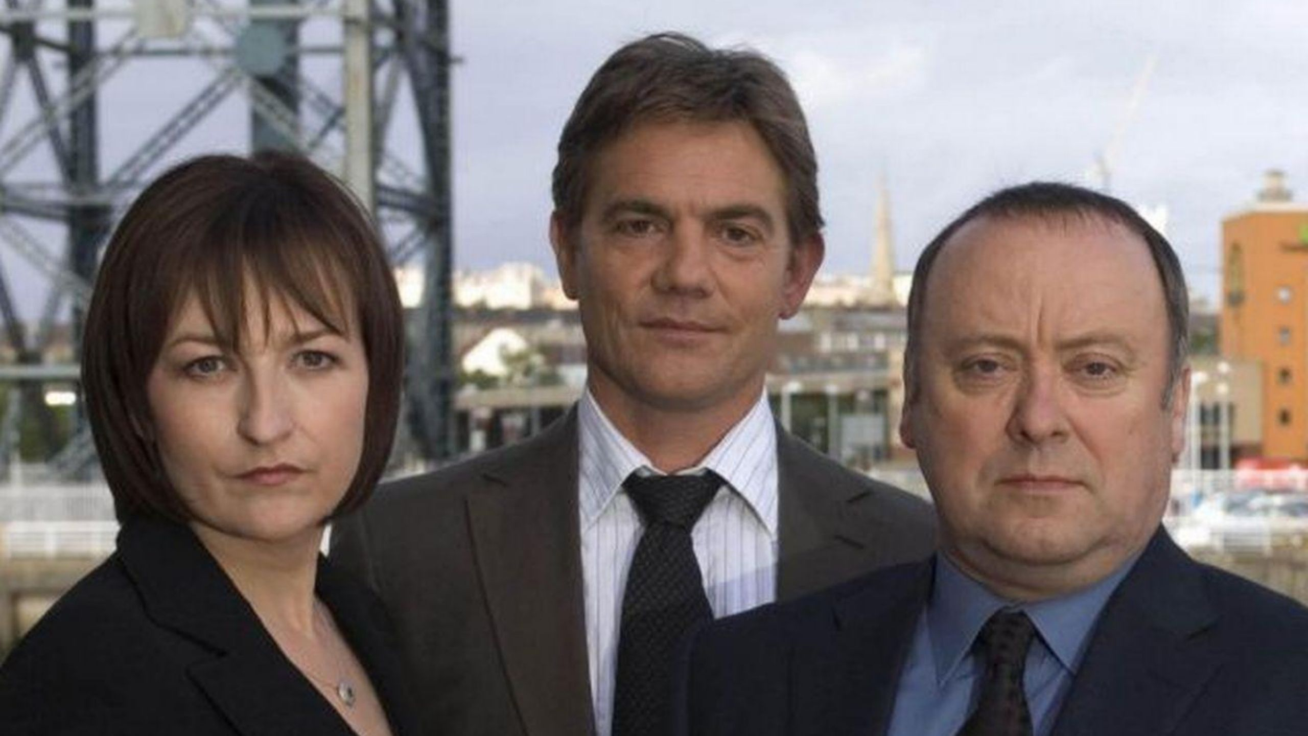 Cast of Taggart dressed in Suits with the Glasgow skyline