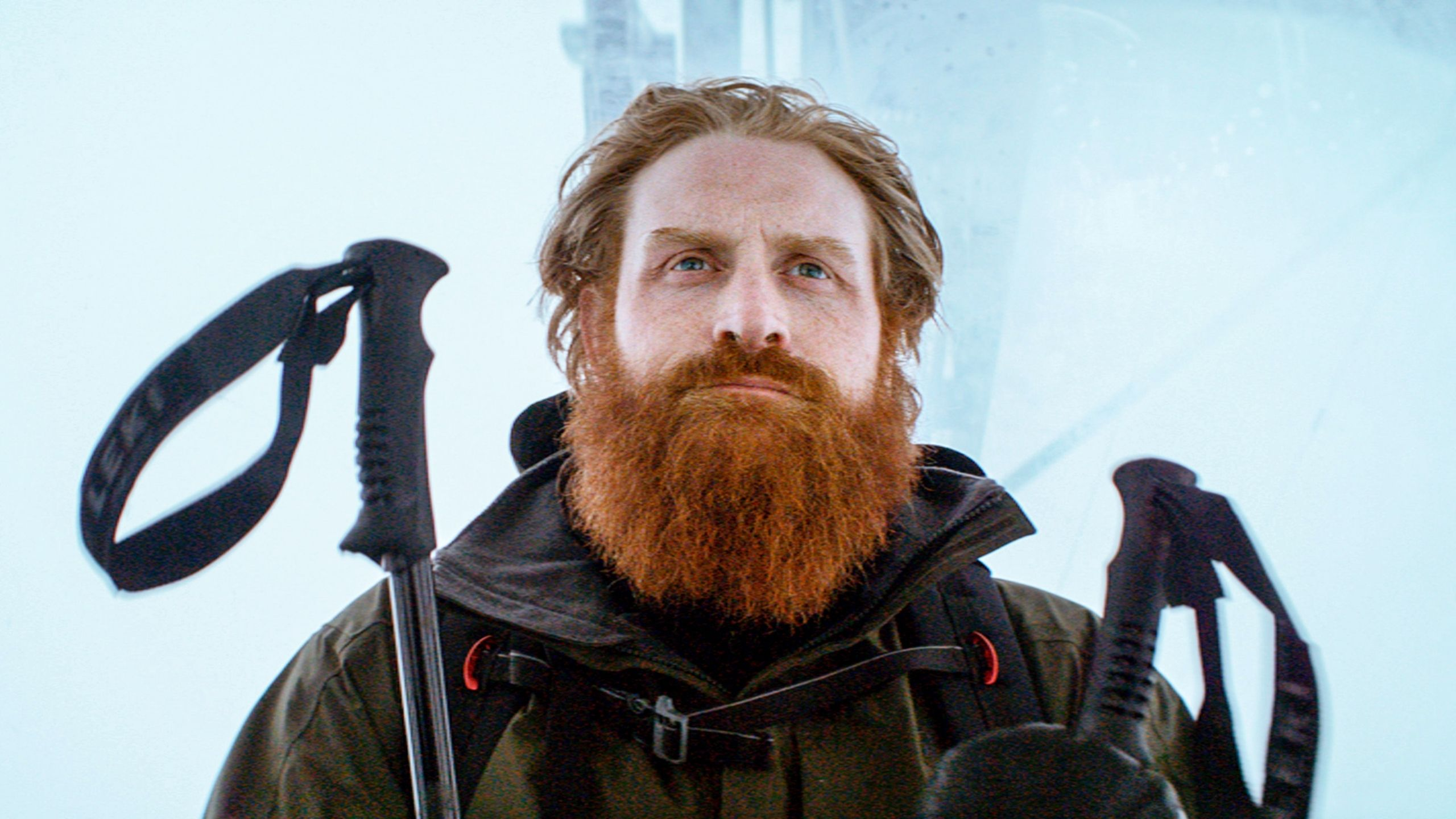 A bearded white man stands in front of a wall of ice, ski sticks in hand.