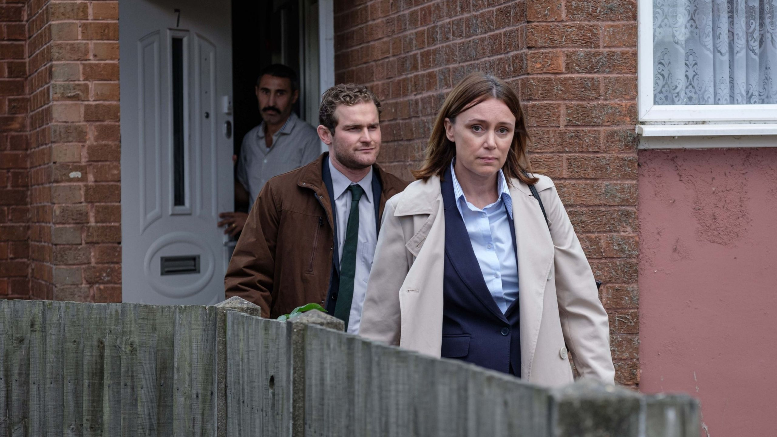 Keeley Hawes as a lead detective shown leaving a house looking tired