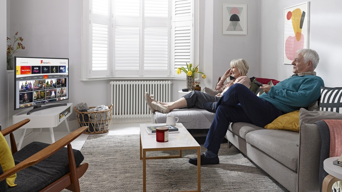 Couple in a living room sitting on a sofa watching TV