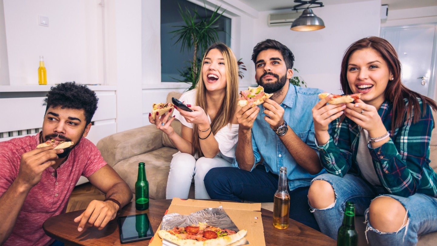 A group of friends watching TV and eating pizza