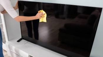 Woman cleaning a TV screen