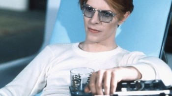 David Bowie starring in The Man who Fell to the Earth, sat on chair wearing blue tinted sunglasses holding a drink