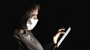 Woman wearing a face mask browsing the internet via a tablet