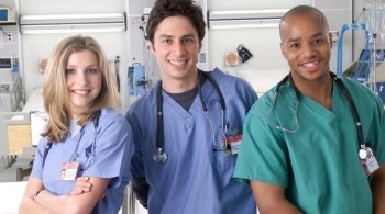 Cast of Scrubs in a hospital smiling at the camera