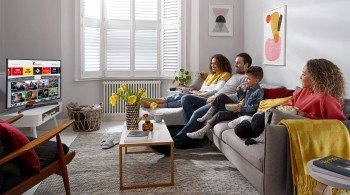 Family relaxing in front of their Freeview Play TV, with the screen showing the on demand line up including STV Player