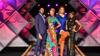 Presenters of Canada Drag Race stand by two colourfully dressed queens on a purple stage