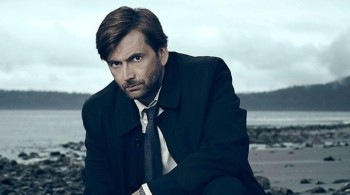 David Tenant as the main detective pictured crouching down on a beach