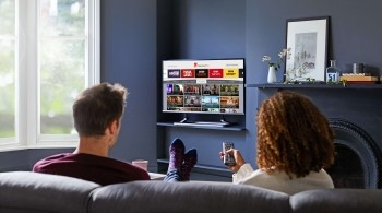 Couple looking at the Explore Freeview Play interface on their TV, about to click onto BBC Sounds