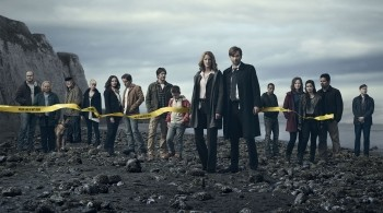 The cast of Gracepoint standing on a beach behind a police line