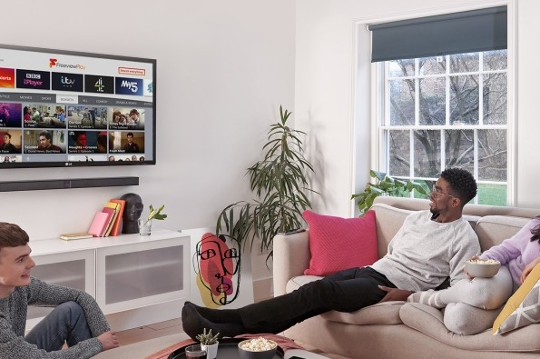 Three young viewers watching Freeview Play on an LG TV